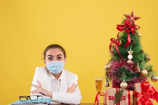クリスマスツリーとギフトボックスと黄色の背景の保護マスクに座っている正面図女性医師 無料写真