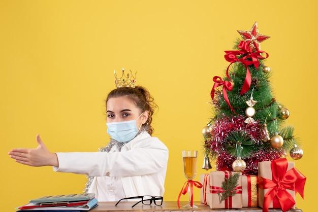 Вид спереди женщина-врач, сидящая в стерильной маске на желтом фоне с елкой и подарочными коробками Бесплатные Фотографии