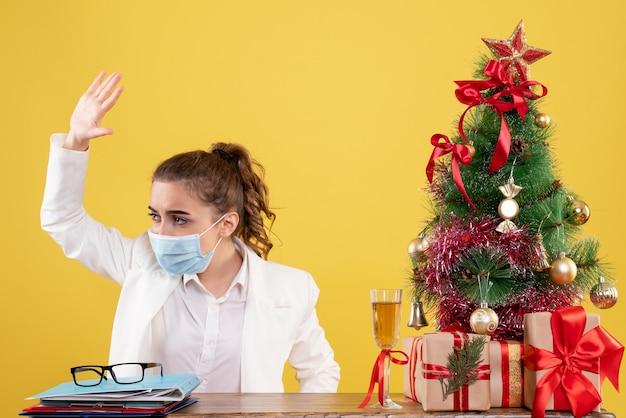 Medico femminile di vista frontale che si siede nella maschera sterile su fondo giallo con l'albero di natale e confezioni regalo Foto Gratuite