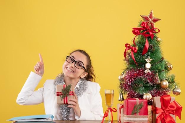 黄色の背景にクリスマスプレゼントと木と一緒に座っている正面図の女性医師 無料写真
