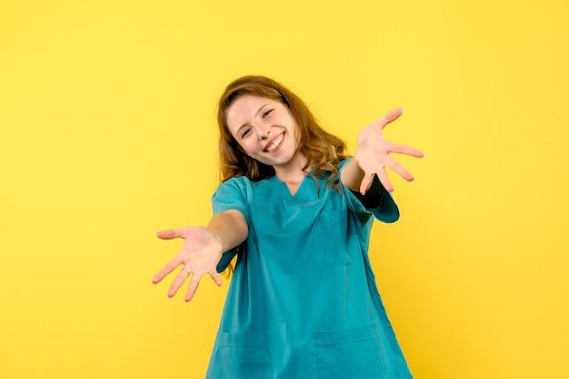 Вид спереди женщина-врач улыбается на желтом пространстве Бесплатные Фотографии