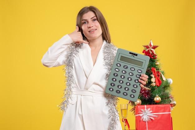 クリスマスツリーとギフトボックスと黄色の背景に電卓を立って保持している女性医師の正面図 無料写真