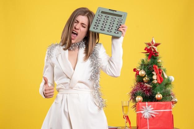전면보기 여성 의사 서 크리스마스 트리와 선물 상자와 노란색 책상에 계산기를 들고 무료 사진