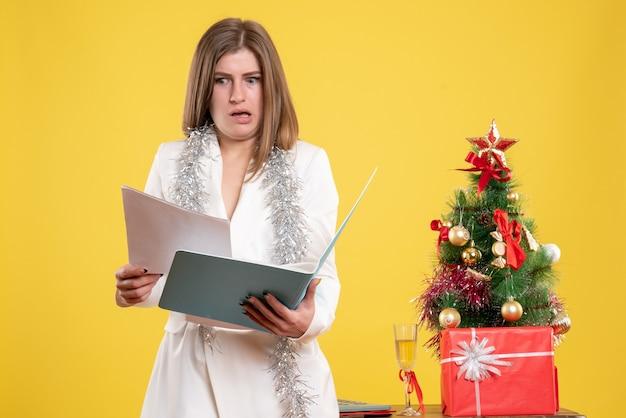 クリスマスツリーとギフトボックスと黄色の背景に立ってドキュメントを保持している正面図の女性医師 無料写真