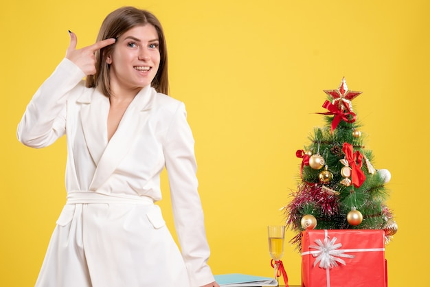 クリスマスプレゼントとクリスマスツリーとギフトボックスと黄色の背景の木とテーブルの周りに立っている正面図の女性医師 無料写真