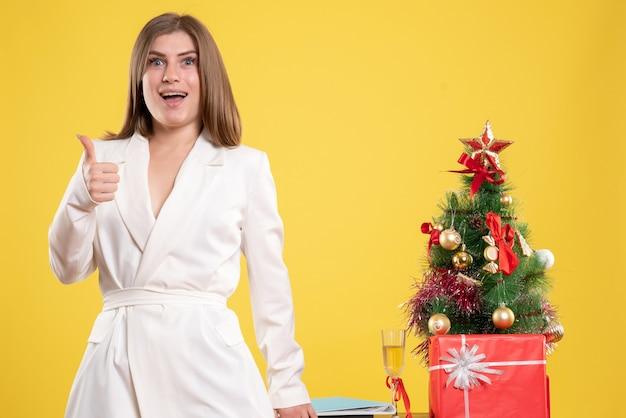 クリスマスツリーとギフトボックスと黄色の背景に小さなクリスマスツリーとテーブルの周りに立っている正面図の女性医師 無料写真