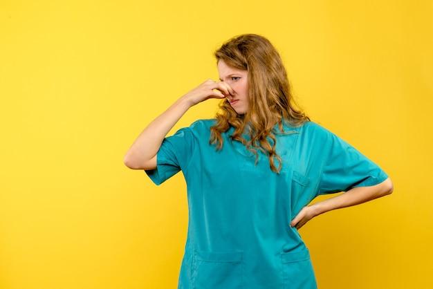 Вид спереди женщина-врач, торчащая носом на желтом пространстве Бесплатные Фотографии