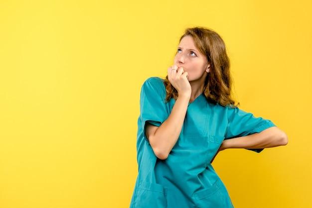 Вид спереди женщина-врач думает на желтом пространстве Бесплатные Фотографии