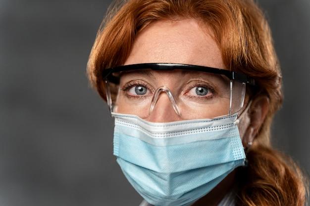 Vista frontale della dottoressa con maschera medica e occhiali di sicurezza Foto Gratuite