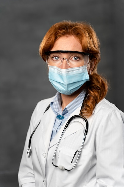 Vista frontale della dottoressa con mascherina medica, stetoscopio e occhiali di sicurezza Foto Gratuite