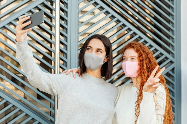Vista frontale di amiche con maschere facciali all'aperto prendendo un selfie Foto Gratuite