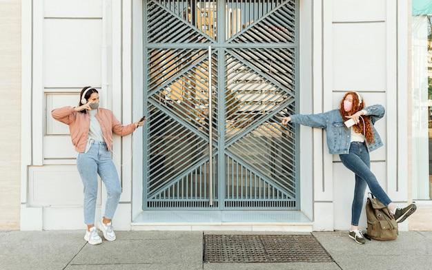 Vista frontale di amiche con maschere facciali all'aperto utilizzando smartphone e balli Foto Gratuite