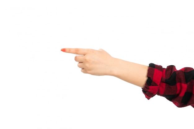 Una mano femminile vista frontale in camicia a scacchi nero-rosso che indica la strada sul bianco Foto Gratuite