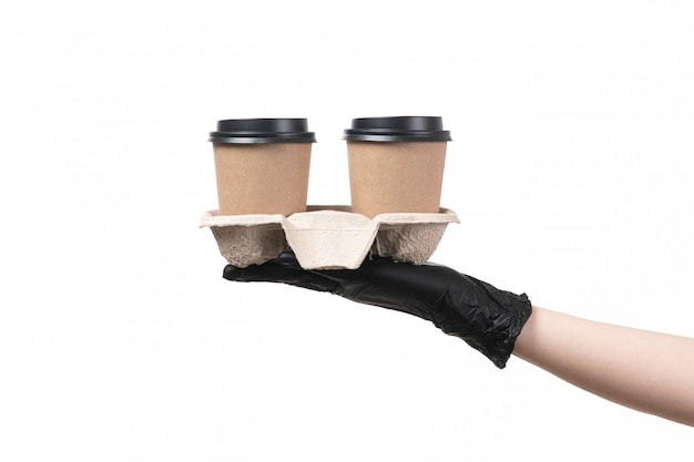 A front view female hand with black gloves holding coffee cups on white Free Photo