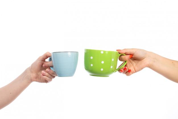 Mani femminili di una vista frontale che tengono le tazze colorate differenti sul bianco Foto Gratuite