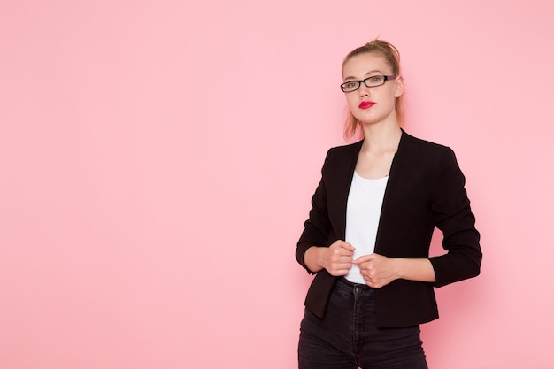 Front view of female office worker in black strict jacket just posing on the pink wall Free Photo