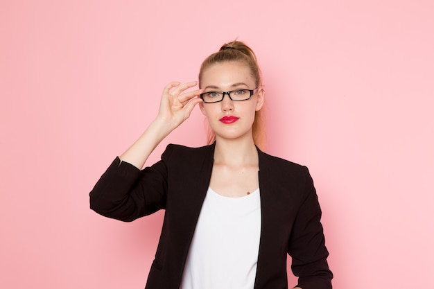 Front view of female office worker in black strict jacket posing touching her sunglasses on light-pink wall Free Photo
