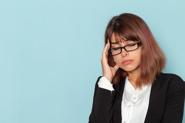 青い表面に頭痛を持っている厳しいスーツの正面図の女性サラリーマン 無料写真