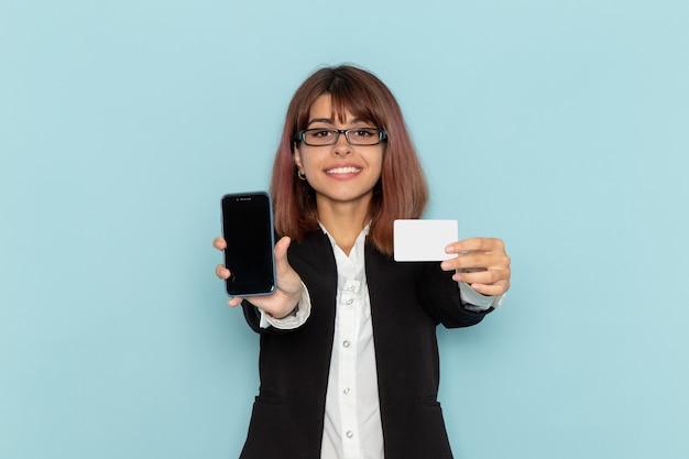 青い表面に白いカードと電話を保持している厳格なスーツの正面の女性サラリーマン 無料写真