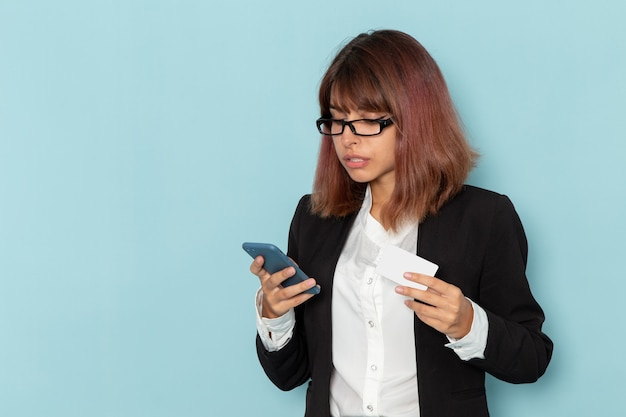 彼女の電話を使用し、水色の表面にカードを保持している正面の女性サラリーマン 無料写真