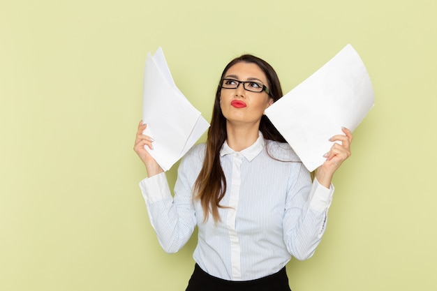 Vista frontale dell'impiegato femminile in camicia bianca e gonna nera che tiene i documenti sulla parete verde Foto Gratuite