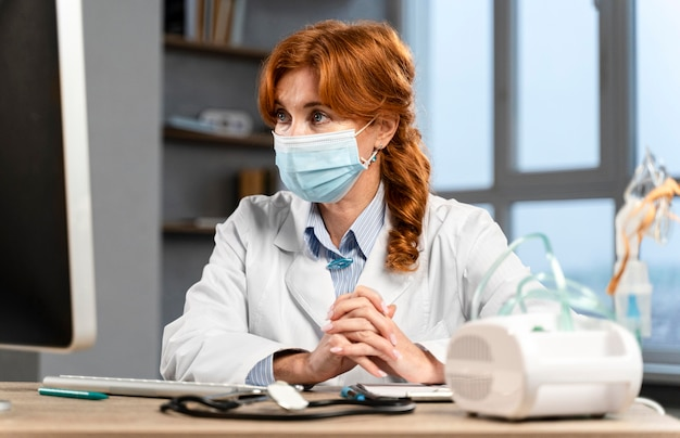 Vista frontale del medico femminile alla sua scrivania con mascherina medica guardando il computer Foto Gratuite