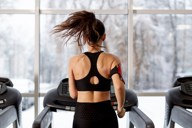 Front view female running on treadmill Free Photo