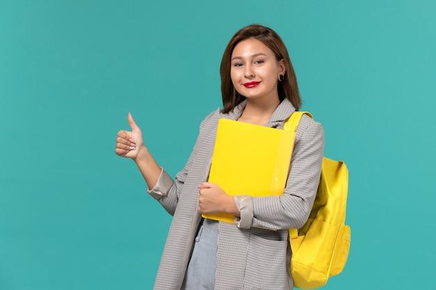 Vista frontale della studentessa in giacca grigia che indossa il suo zaino giallo e che tiene i file sulla parete azzurra Foto Gratuite