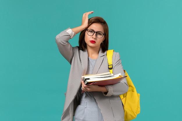 Vista frontale della studentessa in zaino giallo giacca grigia con libri sulla parete blu chiaro Foto Gratuite