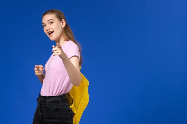 Vista frontale della studentessa in maglietta rosa con zaino giallo in posa sulla parete azzurra Foto Gratuite