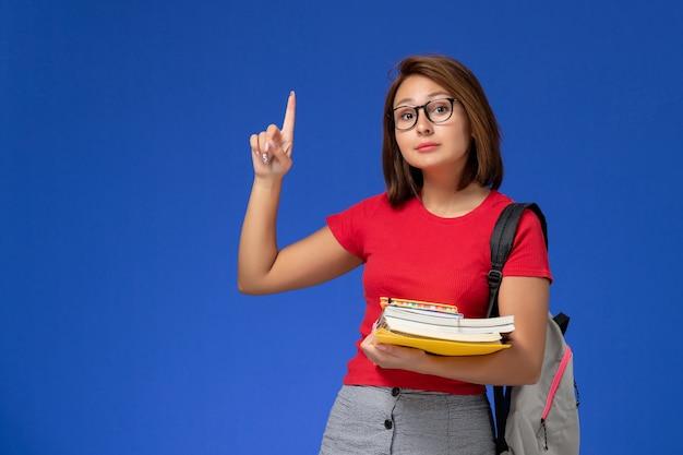 Vista frontale della studentessa in camicia rossa con zaino in possesso di libri e file sulla parete azzurra Foto Gratuite