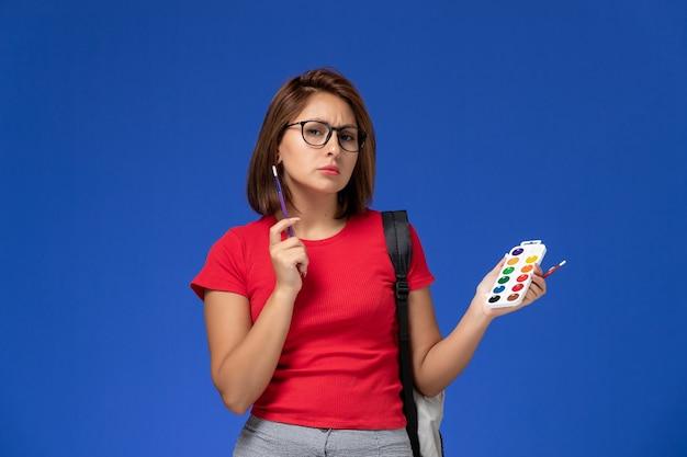 Vista frontale della studentessa in camicia rossa con lo zaino che tiene le vernici per il disegno e le nappe sulla parete blu Foto Gratuite