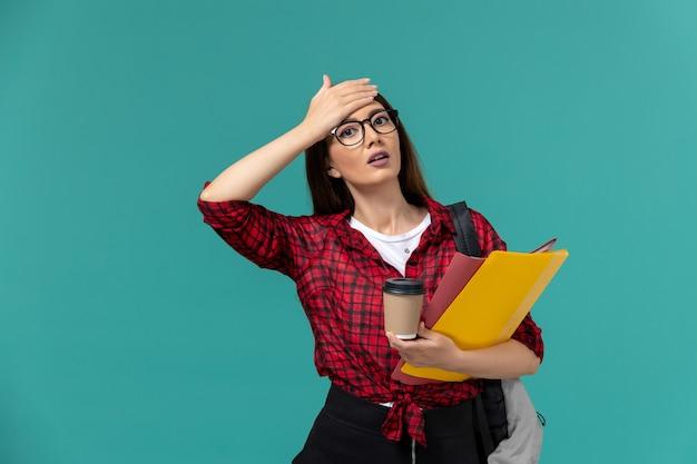 Vista frontale della studentessa che indossa uno zaino che tiene file e caffè sulla parete blu Foto Gratuite