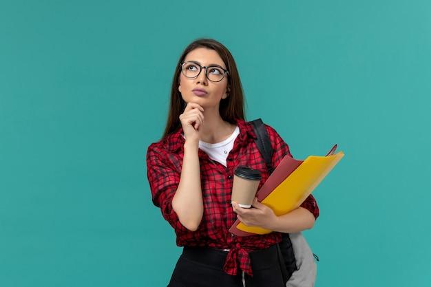 Vista frontale della studentessa che indossa uno zaino in possesso di file e caffè pensando sulla parete azzurra Foto Gratuite