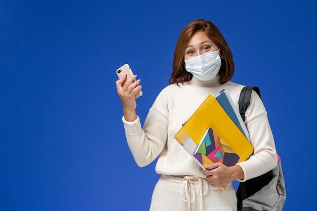 Studentessa di vista frontale in jersey bianco che indossa maschera e zaino tenendo il telefono con le cuffie sulle lezioni di libro dell'università del college della parete blu Foto Gratuite