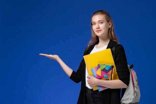 Studentessa di vista frontale in camicia bianca e giacca nera che indossa lo zaino che tiene i file con i quaderni sulle lezioni dell'università dell'università della parete blu Foto Gratuite