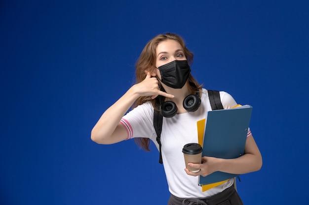 Vista frontale della studentessa in camicia bianca che indossa una maschera sterile nera zaino che tiene caffè e file in posa sulla parete blu Foto Gratuite