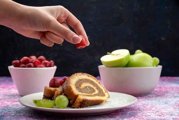 Вид спереди женщина берет малину с тарелки с рулетом вместе с яблоками и малиной на темноте Бесплатные Фотографии