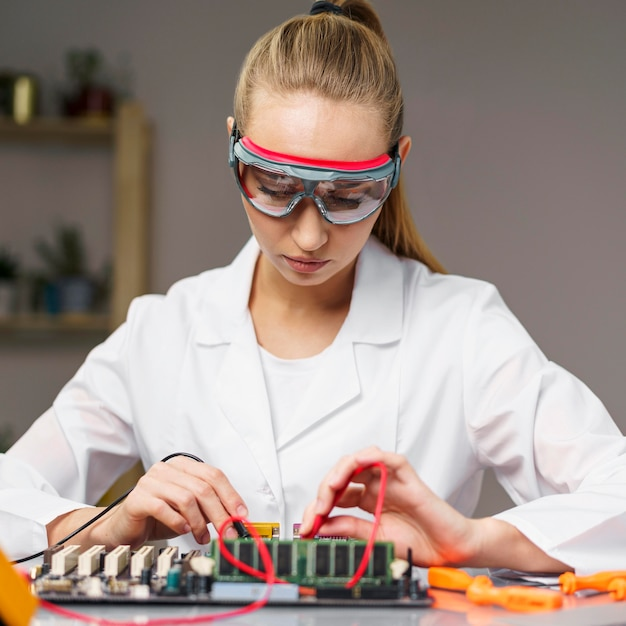 Front view of female technician with soldering iron and electronics motherboard Free Photo