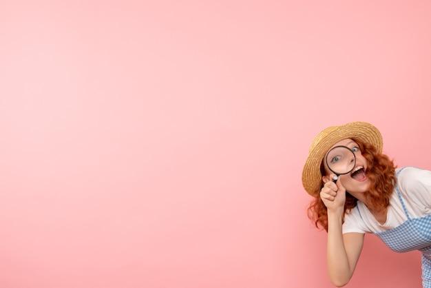 拡大鏡で歩き回る正面図の女性観光客 無料写真
