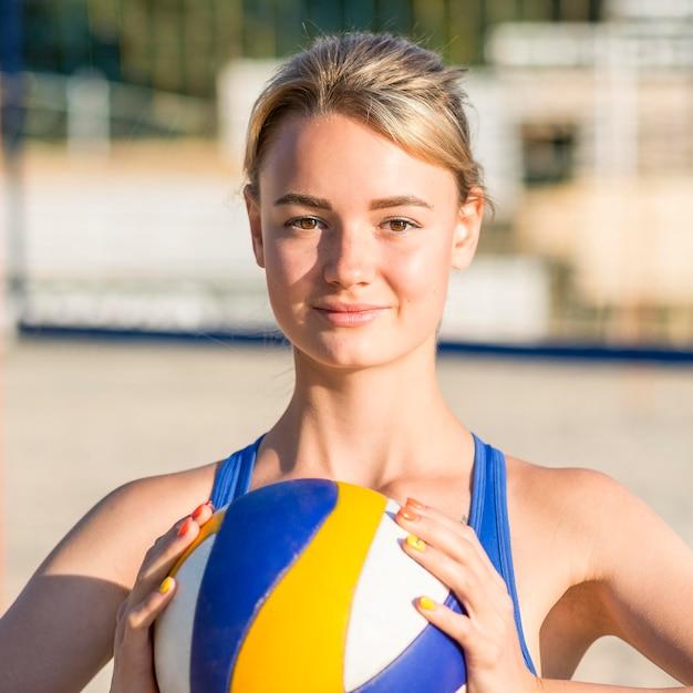 Vista frontale del giocatore di pallavolo femminile sulla sfera della holding della spiaggia Foto Gratuite