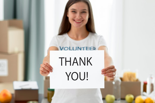 Front view of female volunteer thanking you for helping with food donations Free Photo