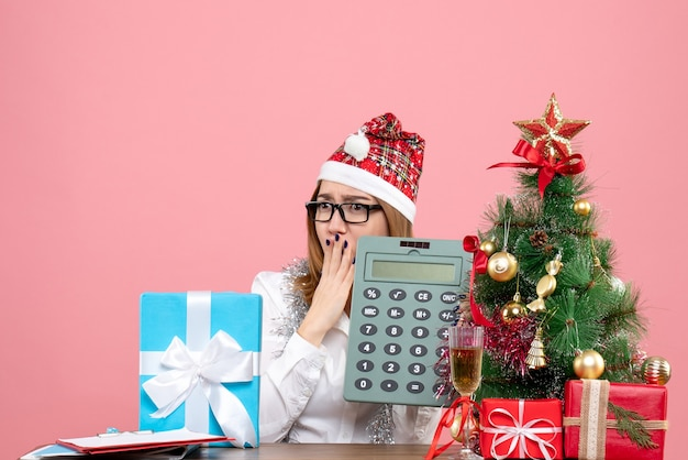Vista frontale della calcolatrice della tenuta della lavoratrice intorno ai regali sul rosa Foto Gratuite
