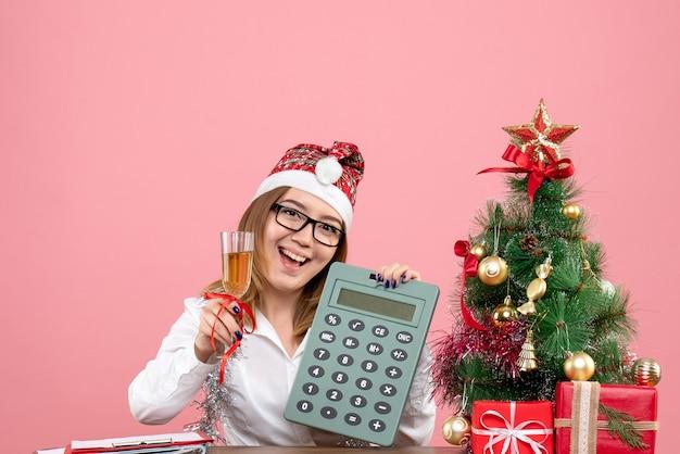 Vista frontale della calcolatrice della tenuta del lavoratore di sesso femminile sul rosa Foto Gratuite