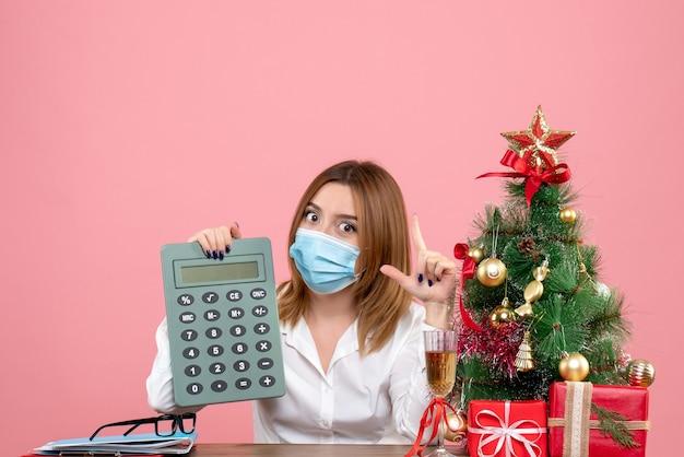 Vista frontale della lavoratrice in maschera sterile tenendo il calcolatore sul rosa Foto Gratuite