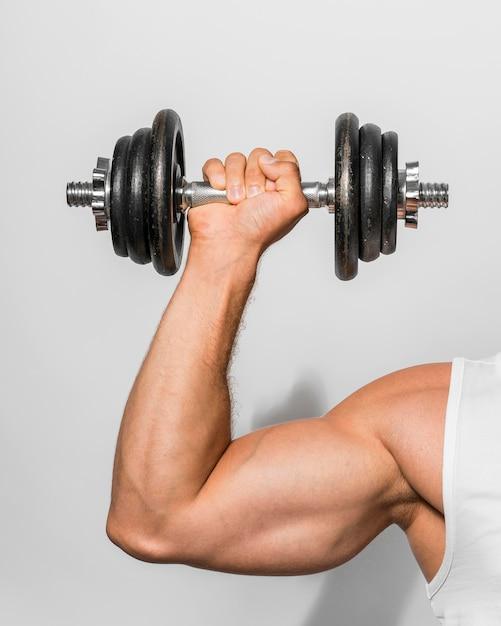 Vista frontale dell'uomo adatto che sostiene i pesi Foto Gratuite