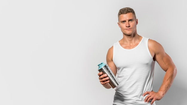 Front view of fit man posing while wearing  tank top and holding water bottle Free Photo