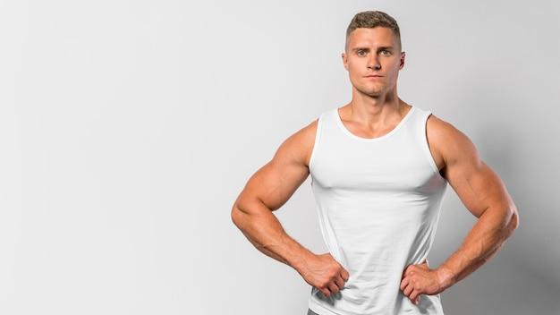 Vista frontale dell'uomo in forma in posa mentre indossa la canotta con lo spazio della copia Foto Gratuite