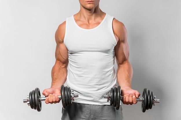 Vista frontale dell'uomo in forma con canotta che lavora con i pesi Foto Gratuite