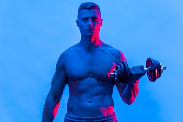 Vista frontale dell'uomo senza camicia adatto che si esercita con i pesi Foto Gratuite